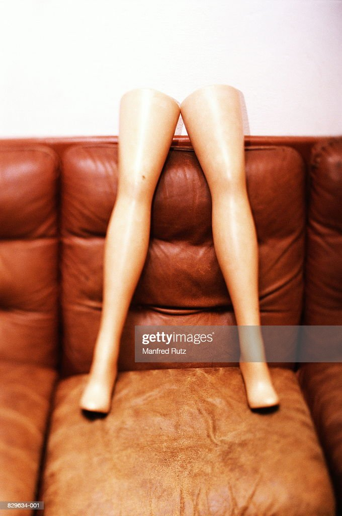 Legs of mannequin standing on sofa