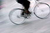 Legs of person riding bicycle.