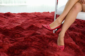 Legs of seated woman wearing red shoes in room with red carpet