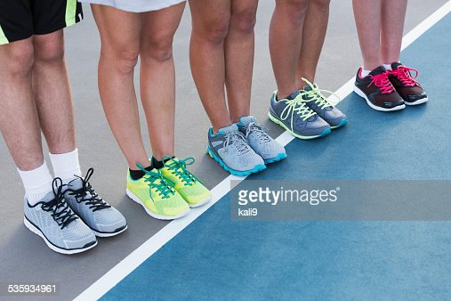 Legs of teenagers standing on tennis court : Stock Photo