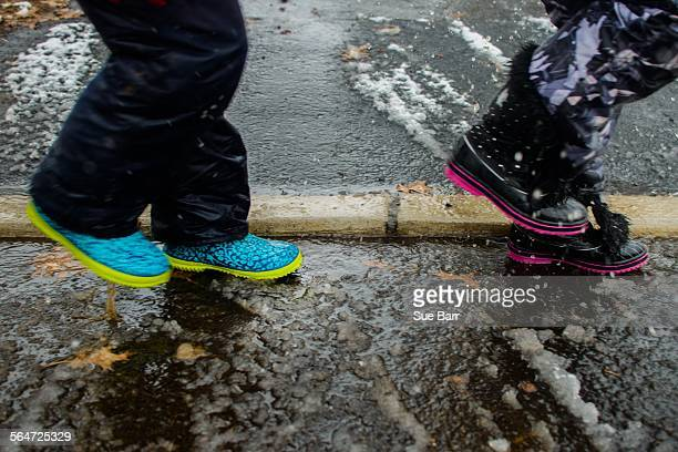 Legs of two girls wearing rubber boots crossing road