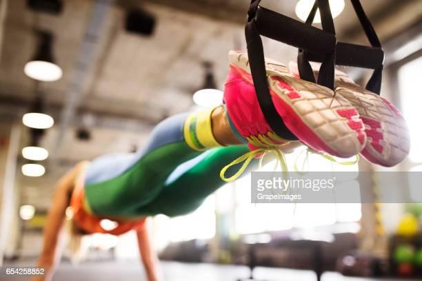 Piernas de mujer irreconocible en el entrenamiento de gimnasio con fitness trx las tiras en la posición de la tabla.