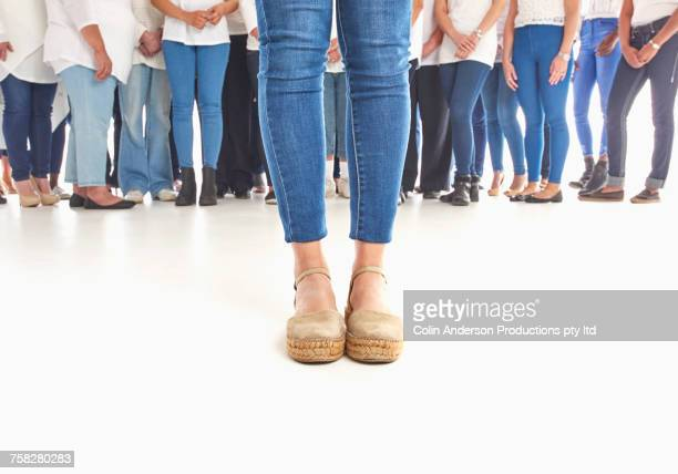 Legs of woman standing out from the crowd