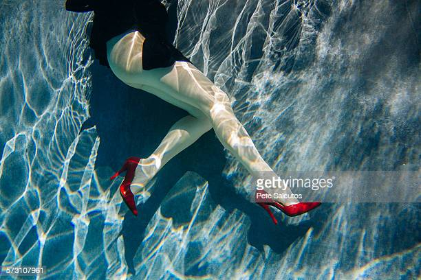 Legs of woman wearing high heels in swimming pool