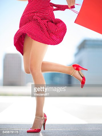 Legs of woman with red skirt and shopping bag