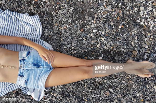 Legs of young beautiful woman lying down on a beach of stones
