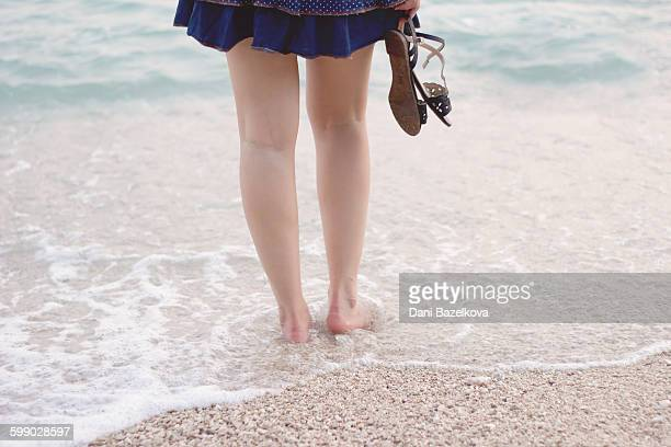 Legs of young woman against the sea