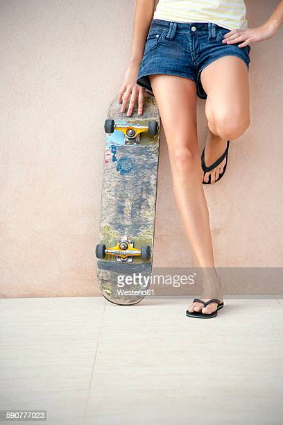 Legs of young woman with longboard in front of a wall