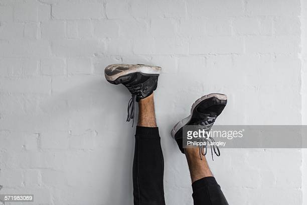 Legs resting upright against wall