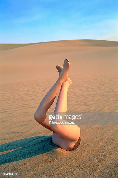 Legs sticking out of sand in desert