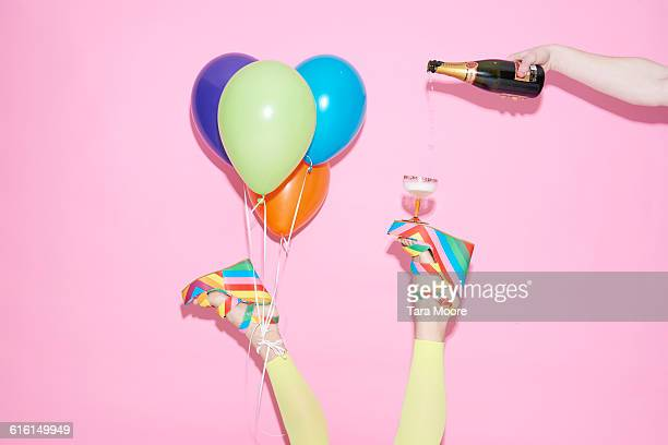 legs with champagne and balloons