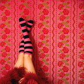 Legs with stockings on wall with flower pattern wallpaper