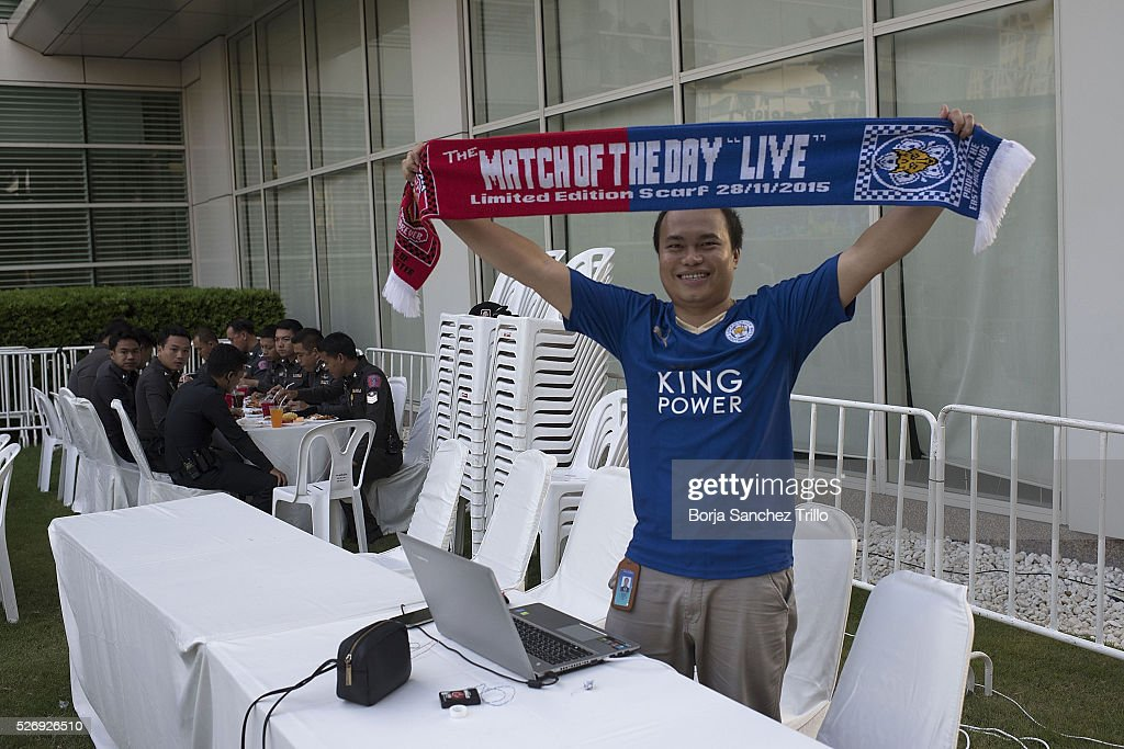 Leicester city fan holds a match scarf of his team as Thai police have dinner behind him before the Manchester United and Leicester City match on May 1, 2016 in Bangkok, Thailand. Leicester City fans gather at King Power Hotel in Bangkok to watch the Premier League game between Manchester United and Leicester City at Old Trafford.