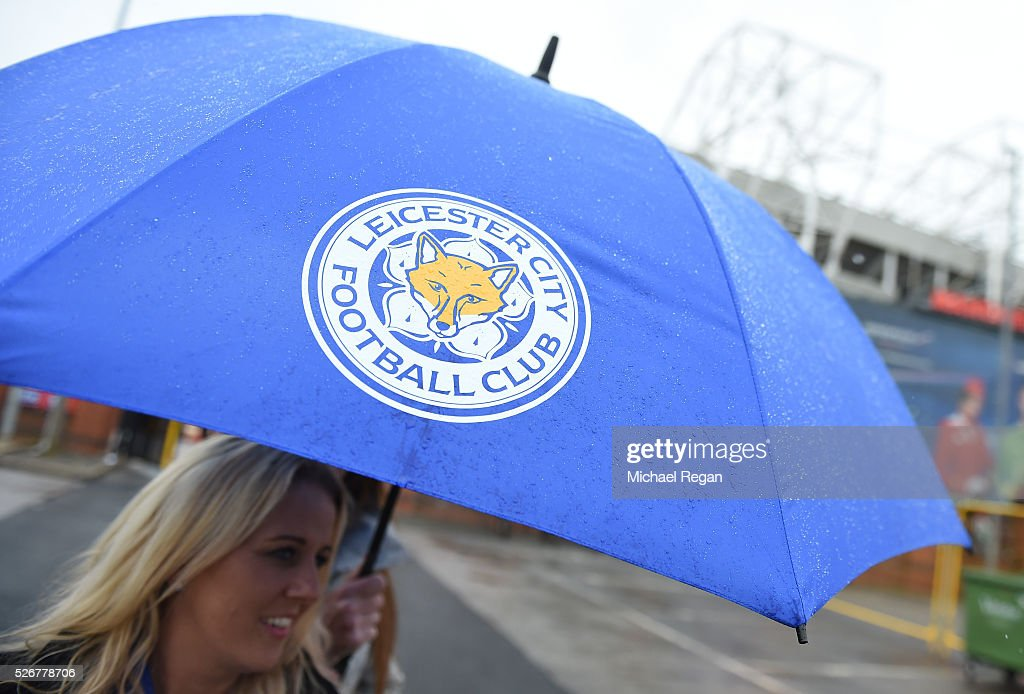 A Leicester City fan shelters from the rain prior to the Barclays Premier League match between Manchester United and Leicester City at Old Trafford on May 1, 2016 in Manchester, England.