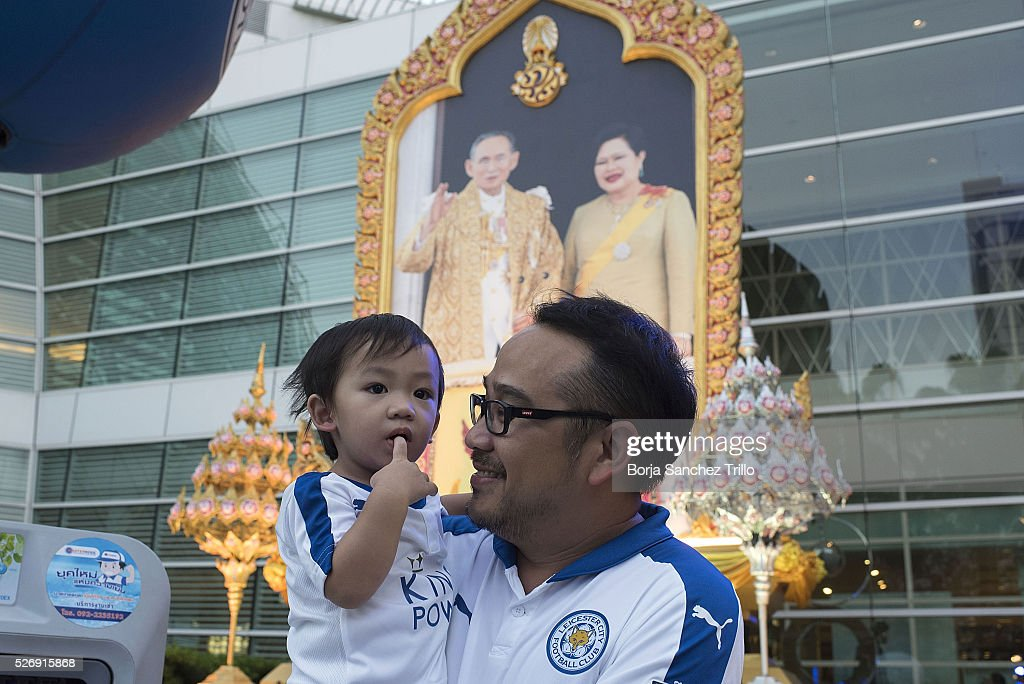 Leicester city fan with his son awaits in front of a Thai King's portrait to watch his team plays against Manchester United on May 1, 2016 in Bangkok, Thailand. Leicester City fans gather at King Power Hotel in Bangkok to watch the Premier League game between Manchester United and Leicester City at Old Trafford.