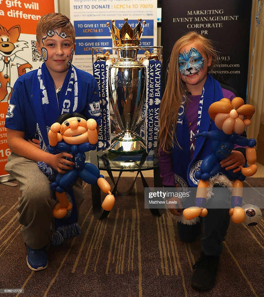 Leicester City fans Bradley and Sophie Robertson pictured with the Barclays Premier League Trophy in a Barclays Bank during a Leicester Backing the Blues Campaign in support of Leicester City on April 29, 2016 in Leicester, England.
