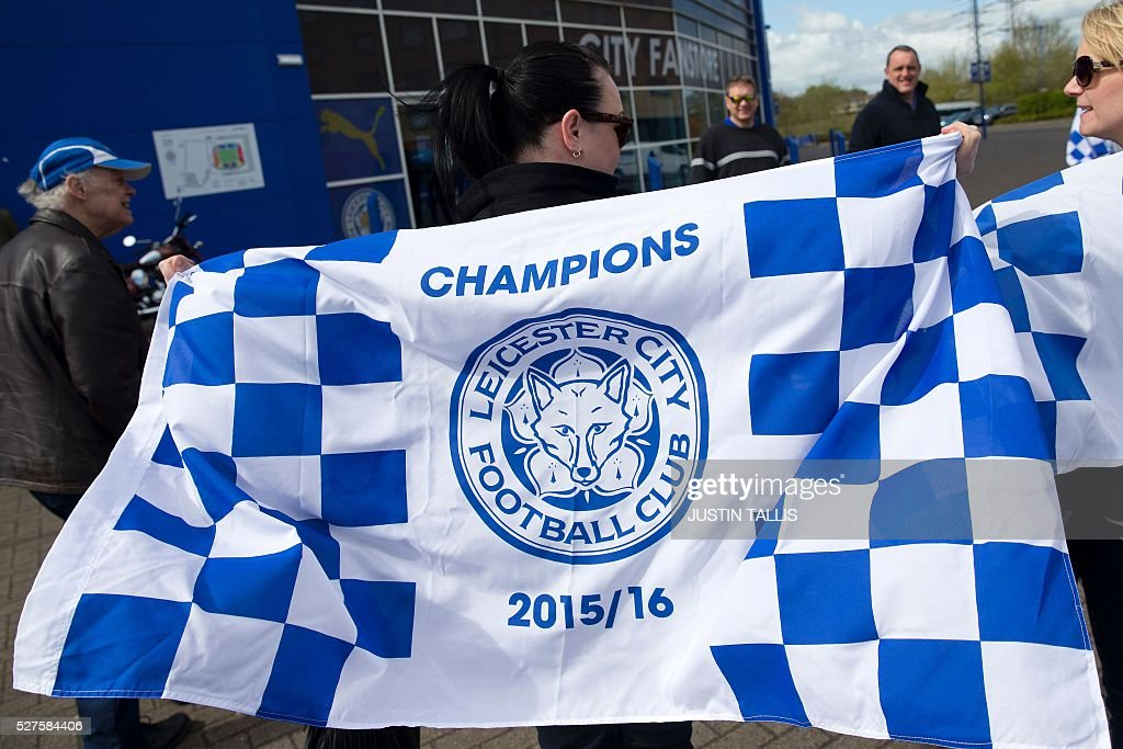 Leicester city fans celebrate outside the King Power Stadium in Leicester, central England, on May 3, 2016, after the team won the English Premier League on Monday May 2. Thousands celebrated and millions around the world watched in wonder as 5,000-1 underdogs Leicester City completed arguably the greatest fairytale in sporting history by becoming English Premier League champions yesterday. Second-placed Tottenham Hotspur's 2-2 draw at Chelsea late on Monday was enough for last year's relegation battlers Leicester to seal a scarcely credible title after outshining some of football's most glamorous teams. / AFP / JUSTIN
