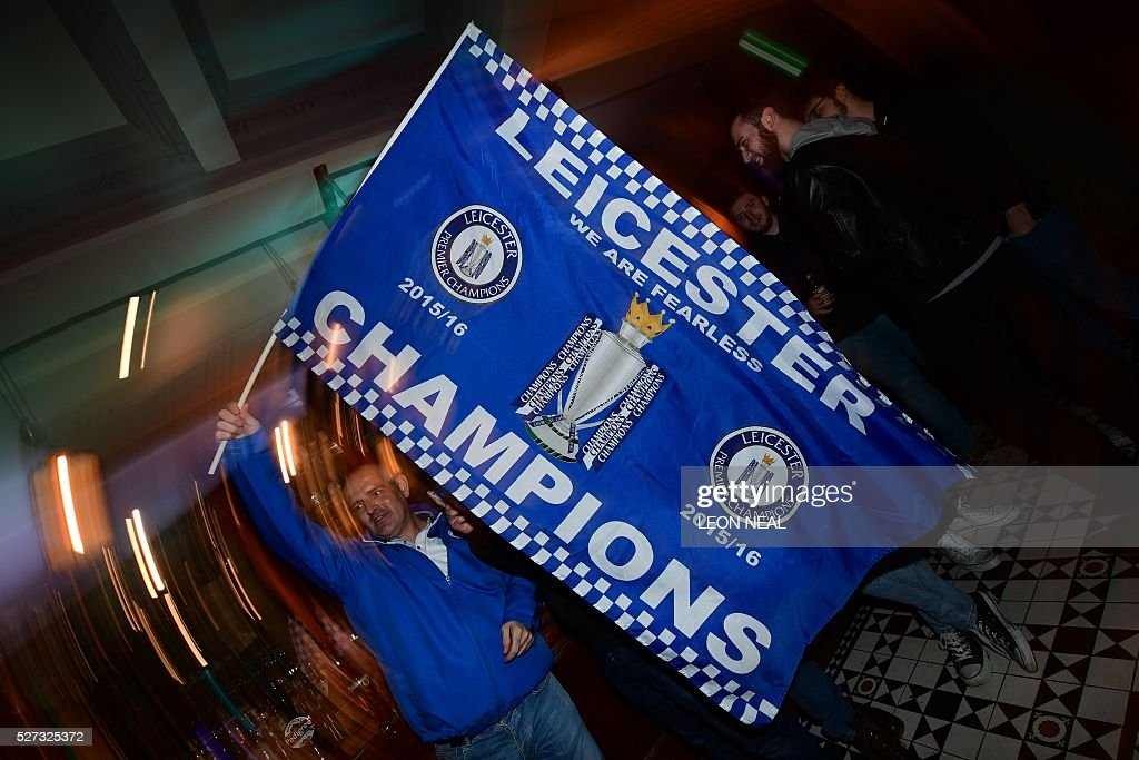 Leicester City fans celebrate winning the football Premier League in central Leicester, eastern England, on May 2, 2016 after Chelsea held Tottenham Hotspur to a 2-2 draw in the English Premier League match. Leicester City completed their fairytale quest for the Premier League title on May 2 after Eden Hazard's stunning late goal earned Chelsea a 2-2 draw with second-place Tottenham Hotspur. NEAL