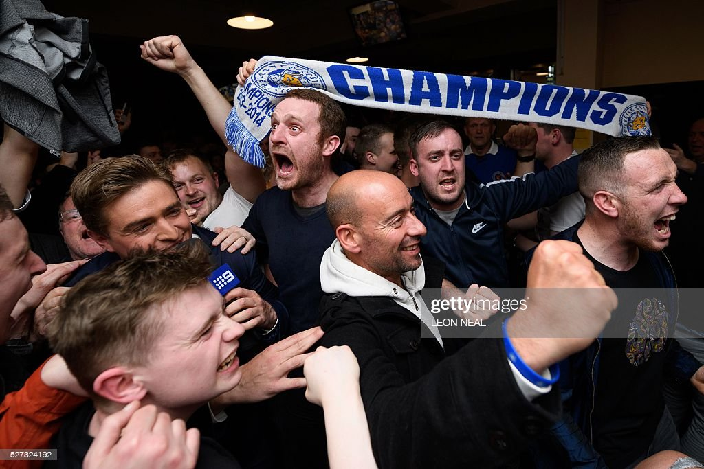 Leicester City fans celebrate winning the Premier League at the final whistle of the English Premier League football match between Chelsea and Tottenham Hotspur in a pub in central Leicester, eastern England, on May 2, 2016. Leicester City completed their fairytale quest for the Premier League title on May 2 after Eden Hazard's stunning late goal earned Chelsea a 2-2 draw with second-place Tottenham Hotspur. NEAL