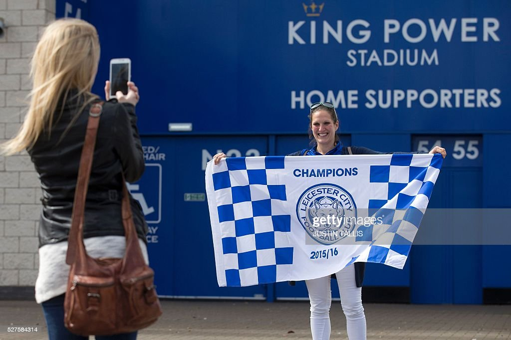 Leicester city fans pose for a photograph as they celebrate outside the King Power Stadium in Leicester, central England, on May 3, 2016, after the team won the English Premier League on Monday May 2. Thousands celebrated and millions around the world watched in wonder as 5,000-1 underdogs Leicester City completed arguably the greatest fairytale in sporting history by becoming English Premier League champions yesterday. Second-placed Tottenham Hotspur's 2-2 draw at Chelsea late on Monday was enough for last year's relegation battlers Leicester to seal a scarcely credible title after outshining some of football's most glamorous teams. / AFP / JUSTIN