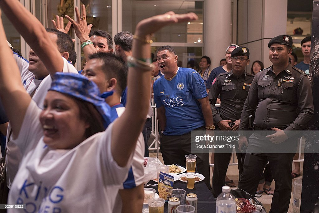 Leicester city fans react while watching their team plays against Manchester United as Thai police stand guard on May 1, 2016 in Bangkok, Thailand. Leicester City fans gather at King Power Hotel in Bangkok to watch the Premier League game between Manchester United and Leicester City at Old Trafford.