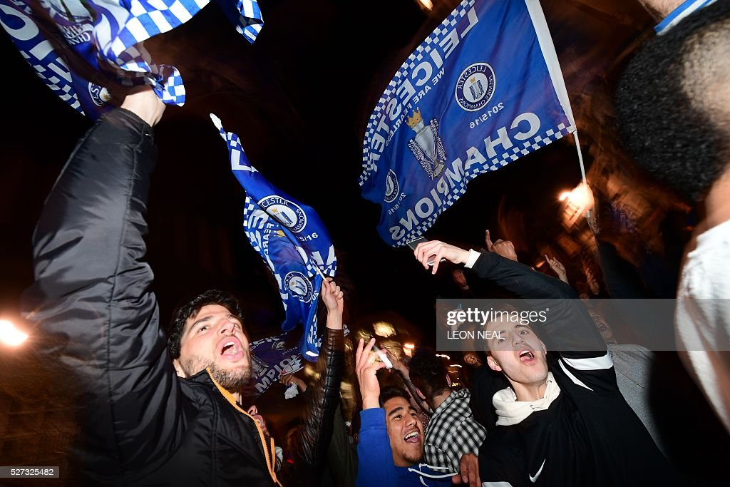 Leicester City fans wave flags as they celebrates their team becoming the English Premier League football champions in central Leicester, eastern England, on May 2, 2016 after Chelsea held Tottenham Hotspur to a 2-2 draw in the English Premier League match. Leicester City completed their fairytale quest for the Premier League title on May 2 after Eden Hazard's stunning late goal earned Chelsea a 2-2 draw with second-place Tottenham Hotspur. NEAL