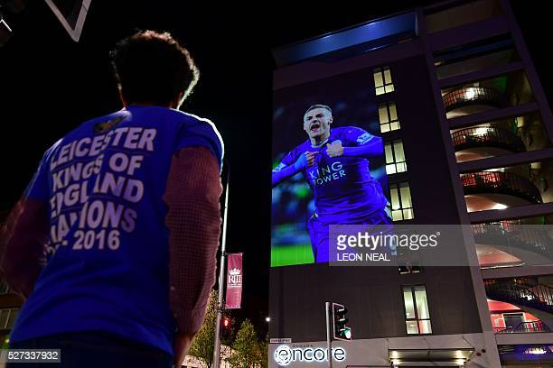 Leicester City football fan looks up at a large projection of an image of Leicester City's striker Jamie Vardy on the side of a building as the city...