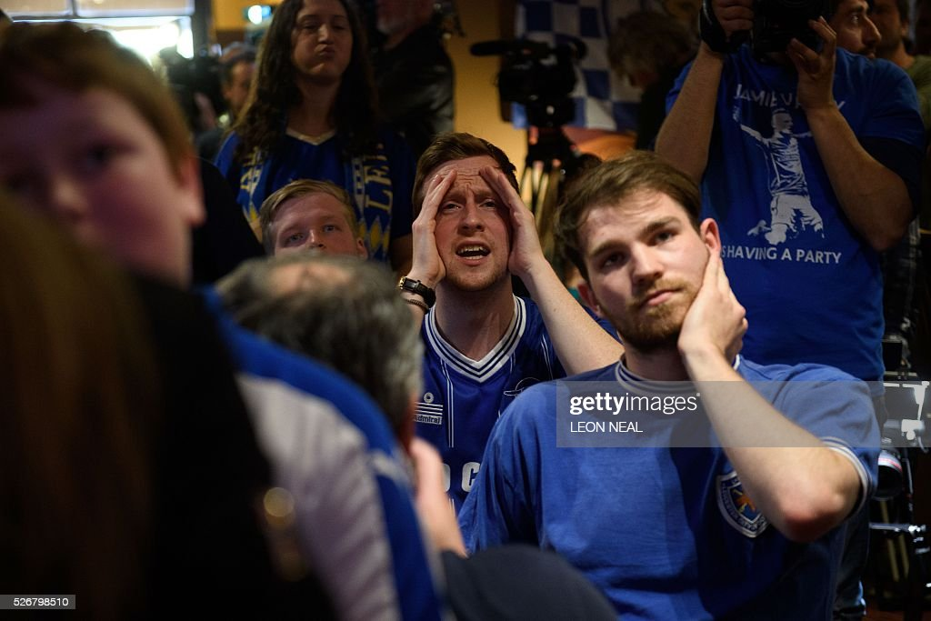 Leicester City football fans react as they watch the English Premier League football match between Leicester City and Manchester United match in a pub in Leicester, eastern England, on 1 May, 2016. Leicester City will win the Premier League if they beat Manchester United in the match at Old Trafford. / AFP / LEON