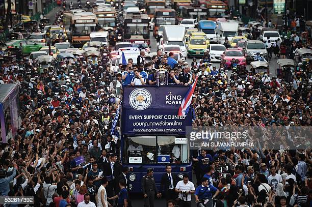 TOPSHOT Leicester City football players and staff stand with the Premier League trophy whilst surrounded by fans during the openbus parade in Bangkok...