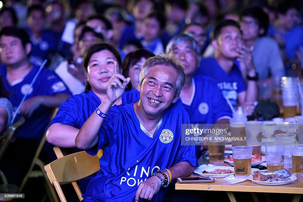 Leicester City football supporters react as they watch a live broadcast of the English Premier League football match between Manchester United and Leicester City played at Old Trafford in Manchester, on May 1, 2016 in Bangkok. / AFP / CHRISTOPHE