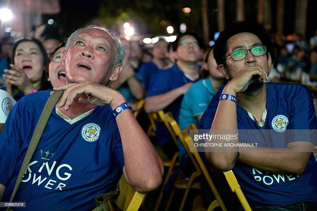 Leicester City football supporters watch on May 1, 2016 in Bangkok, a live broadcast of the English Premier League football match between Manchester United and Leicester City played at Old Trafford in Manchester. Leicester made to wait for title triumph after 1-1 draw at Manchester United, but will be crowned champions if Tottenham fail to beat Chelsea on May 2, 2016. / AFP / CHRISTOPHE