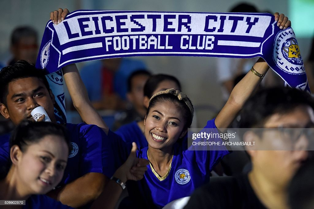 A Leicester City football woman supporter react on May 1, 2016 in Bangkok, as she watches a live broadcast of the English Premier League football match between Manchester United and Leicester City played at Old Trafford in Manchester. Leicester made to wait for title triumph after 1-1 draw at Manchester United, but will be crowned champions if Tottenham fail to beat Chelsea on May 2, 2016. / AFP / CHRISTOPHE