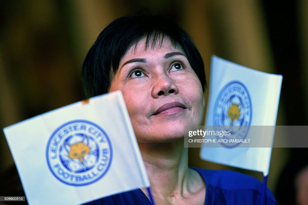 A Leicester City football woman supporter watches on May 1, 2016 in Bangkok, a live broadcast of the English Premier League football match between Manchester United and Leicester City played at Old Trafford in Manchester. Leicester made to wait for title triumph after 1-1 draw at Manchester United, but will be crowned champions if Tottenham fail to beat Chelsea on May 2, 2016. / AFP / CHRISTOPHE