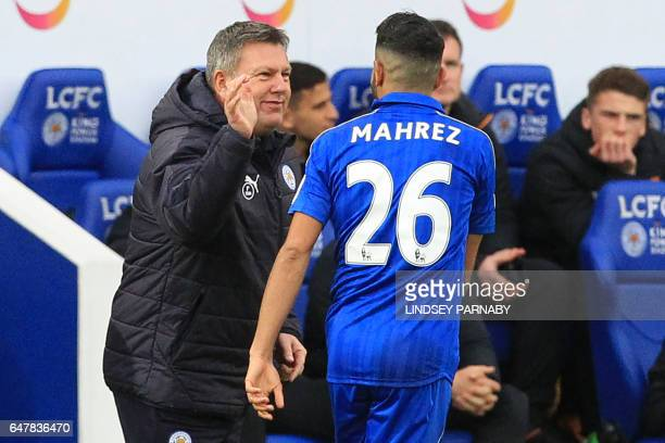 Leicester City's Algerian midfielder Riyad Mahrez celebrates with Leicester City's English interim manager Craig Shakespeare after scoring their...