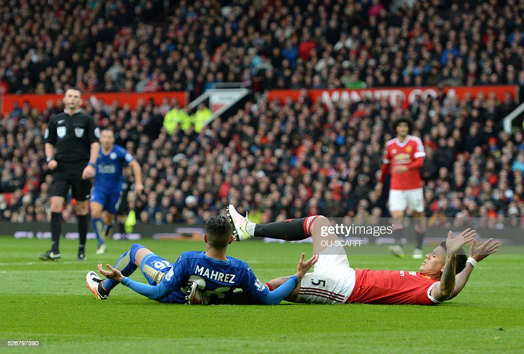 Leicester City's Algerian midfielder Riyad Mahrez (C floor) goes down in a collision with Manchester United's Argentinian defender Marcos Rojo (R), no foul given, during the English Premier League football match between Manchester United and Leicester City at Old Trafford in Manchester, north west England, on May 1, 2016. / AFP / OLI SCARFF / RESTRICTED TO EDITORIAL USE. No use with unauthorized audio, video, data, fixture lists, club/league logos or 'live' services. Online in-match use limited to 75 images, no video emulation. No use in betting, games or single club/league/player publications. /