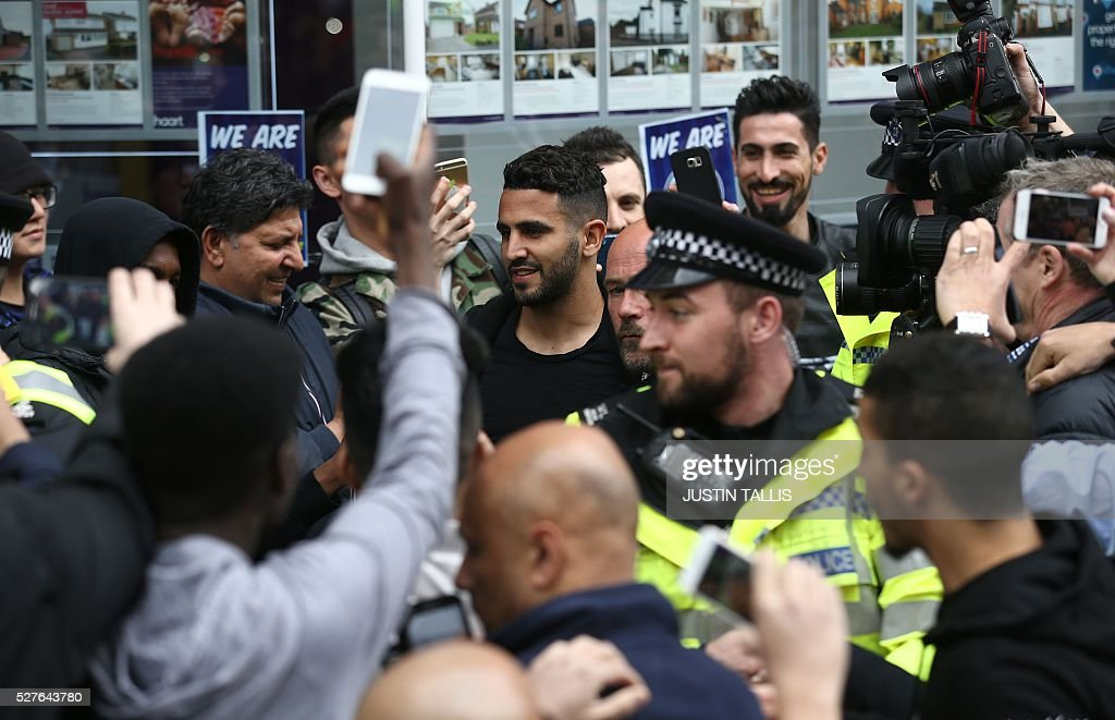 Leicester City's Algerian midfielder Riyad Mahrez (C) is helped to a car as he makes his way through crowds of fans after having lunch with team-mates an Italian restaurant in the centre of Leicester on May 3, 2016, the day after winning the English Premier League title. Thousands celebrated and millions around the world watched in wonder as 5,000-1 underdogs Leicester City completed arguably the greatest fairytale in sporting history by becoming English Premier League champions. / AFP / JUSTIN
