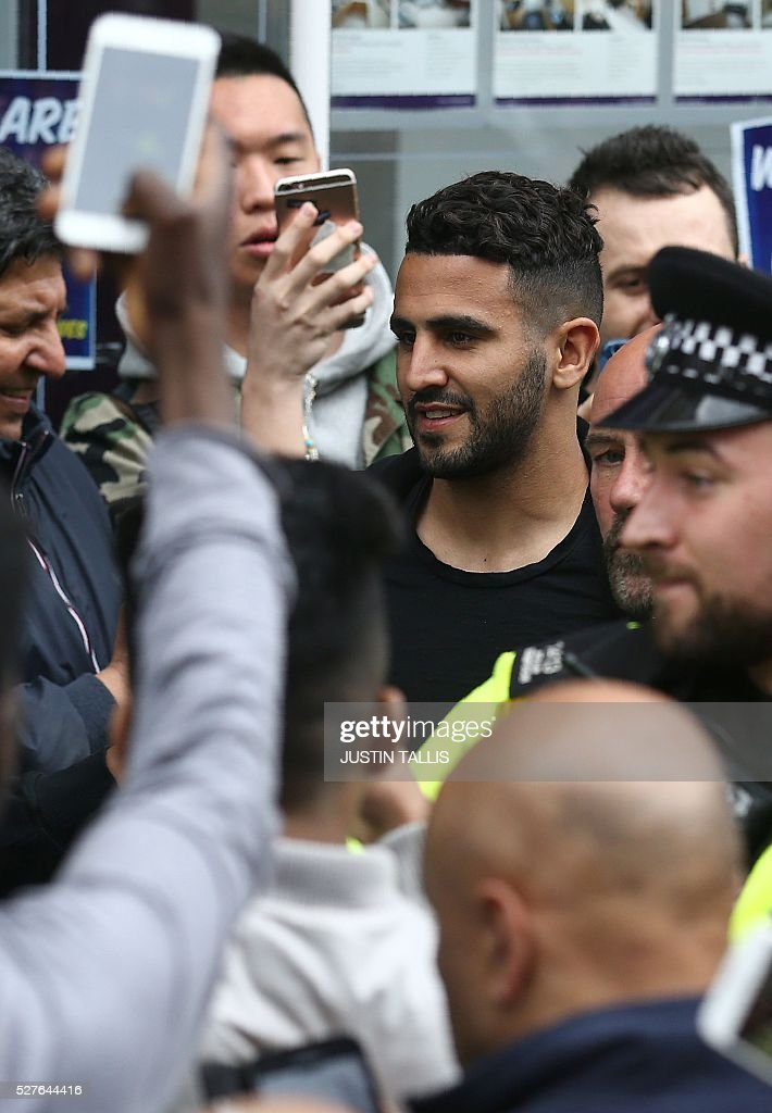 Leicester City's Algerian midfielder Riyad Mahrez (C) reacts as he is helped to a car whilst making his way through crowds of fans after having lunch with team-mates an Italian restaurant in the centre of Leicester on May 3, 2016, the day after winning the English Premier League title. Thousands celebrated and millions around the world watched in wonder as 5,000-1 underdogs Leicester City completed arguably the greatest fairytale in sporting history by becoming English Premier League champions. / AFP / JUSTIN