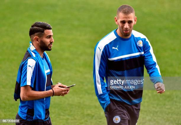 Leicester City's Algerian midfielder Riyad Mahrez speaks with Leicester City's Algerian striker Islam Slimani before a training session at the...