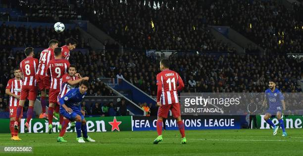 Leicester City's Algerian midfielder Riyad Mahrez watches the ball after taking a free kick during the UEFA Champions League quarterfinal second leg...