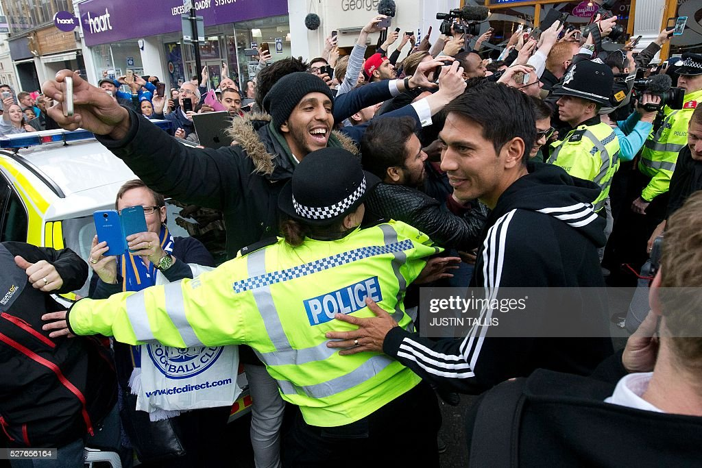 Leicester City's Argentinian footballer Leonardo Ulloa (R) is mobbed by fans as he leaves an Italian restaurant after having lunch with team-mates in the centre of Leicester on May 3, 2016, the day after winning the English Premier League title. Thousands celebrated and millions around the world watched in wonder as 5,000-1 underdogs Leicester City completed arguably the greatest fairytale in sporting history by becoming English Premier League champions. / AFP / JUSTIN