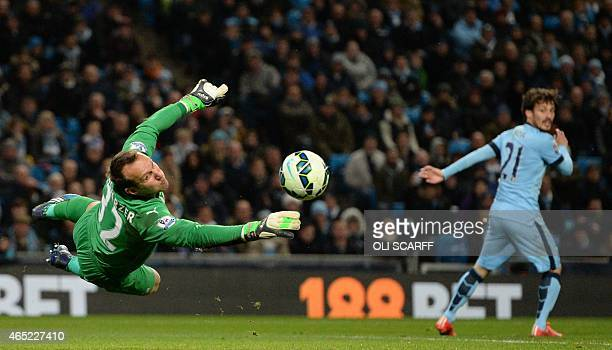 Leicester City's Australian goalkeeper Mark Schwarzer makes a save from a shot by Manchester City's Argentinian striker Sergio Aguero as Manchester...