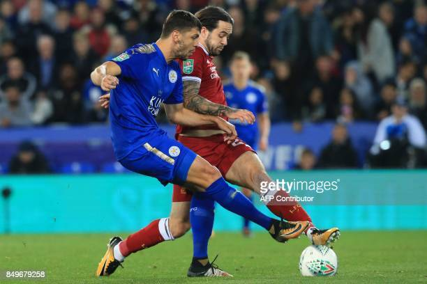 Leicester City's Austrian defender Aleksandar Dragovic vies with Liverpool's English striker Danny Ings during the English League Cup third round...