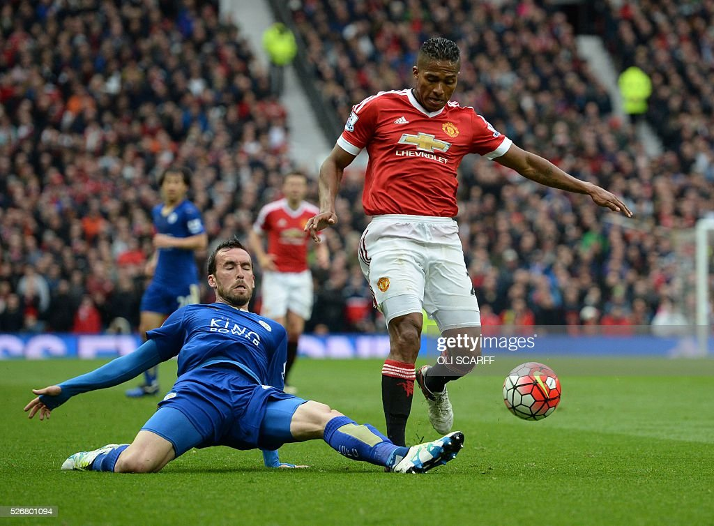 Leicester City's Austrian defender Christian Fuchs (L) slides to tackle Manchester United's Ecuadorian midfielder Antonio Valencia (R) during the English Premier League football match between Manchester United and Leicester City at Old Trafford in Manchester, north west England, on May 1, 2016. / AFP / OLI SCARFF / RESTRICTED TO EDITORIAL USE. No use with unauthorized audio, video, data, fixture lists, club/league logos or 'live' services. Online in-match use limited to 75 images, no video emulation. No use in betting, games or single club/league/player publications. /
