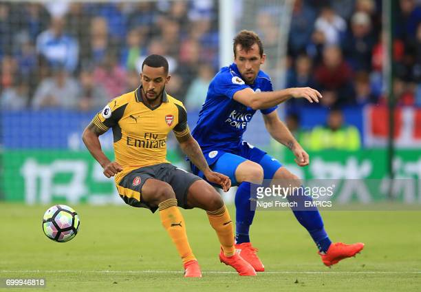 Leicester City's Christian Fuchs and Arsenal's Theo Walcott battle for the ball