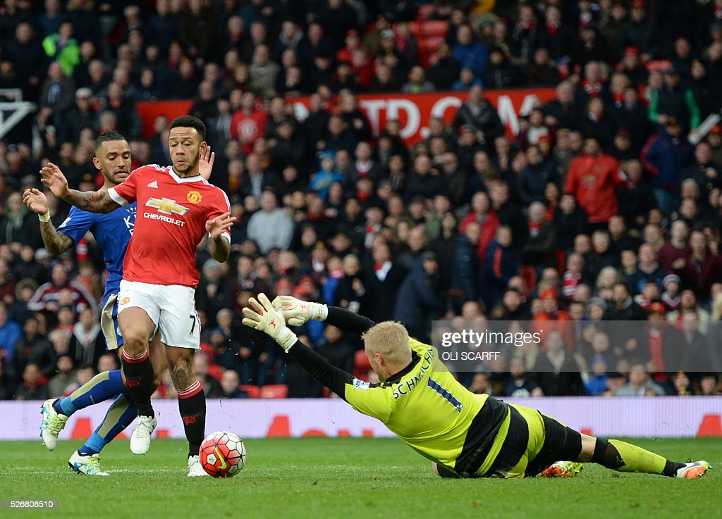 Leicester City's Danish goalkeeper Kasper Schmeichel (R) comes out to make a save from Manchester United's Dutch midfielder Memphis Depay (C) during the English Premier League football match between Manchester United and Leicester City at Old Trafford in Manchester, north west England, on May 1, 2016. / AFP / OLI SCARFF / RESTRICTED TO EDITORIAL USE. No use with unauthorized audio, video, data, fixture lists, club/league logos or 'live' services. Online in-match use limited to 75 images, no video emulation. No use in betting, games or single club/league/player publications. /