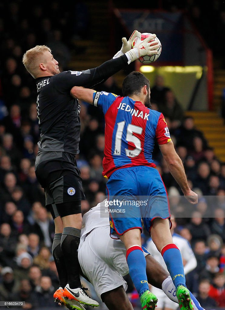 Leicester City's Danish goalkeeper Kasper Schmeichel (L) defends against Crystal Palace's Mile Jedinak during the English Premier League football match between Crystal Palace and Leicester City at Selhurst Park in south London on March 19, 2016. / AFP / IKIMAGES / IKimages / RESTRICTED TO EDITORIAL USE. No use with unauthorized audio, video, data, fixture lists, club/league logos or 'live' services. Online in-match use limited to 45 images, no video emulation. No use in betting, games or single club/league/player publications. /