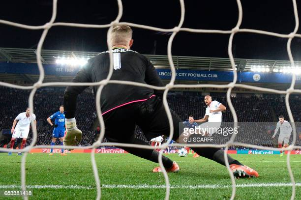 Leicester City's Danish goalkeeper Kasper Schmeichel dives to save a penalty taken by Sevilla's French midfielder Steven N'Zonzi during the UEFA...