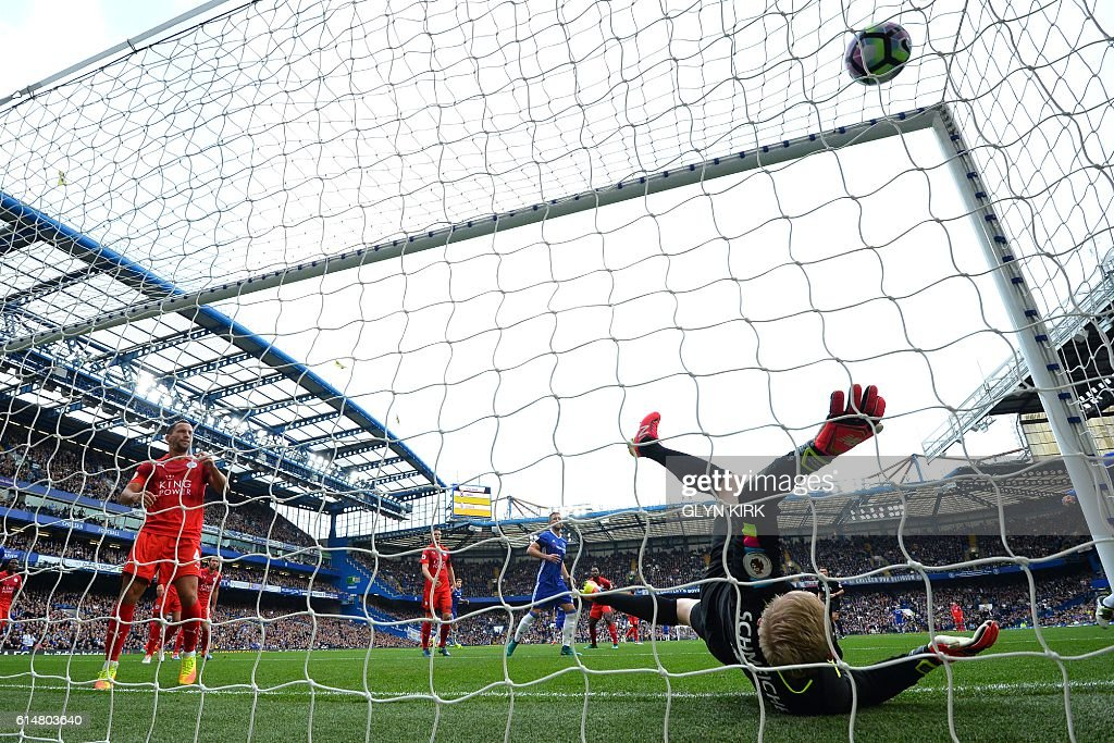 Leicester City's Danish goalkeeper Kasper Schmeichel (R) falls after failing to stop a goal by Chelsea's Brazilian-born Spanish striker Diego Costa during the English Premier League football match between Chelsea and Leicester City at Stamford Bridge in London on October 15, 2016. / AFP / GLYN KIRK / RESTRICTED TO EDITORIAL USE. No use with unauthorized audio, video, data, fixture lists, club/league logos or 'live' services. Online in-match use limited to 75 images, no video emulation. No use in betting, games or single club/league/player publications. /
