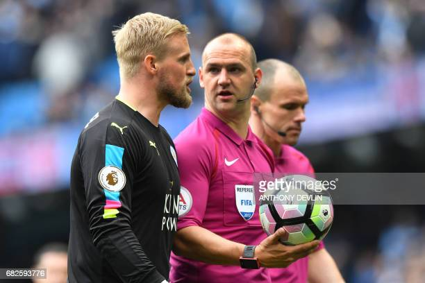 Leicester City's Danish goalkeeper Kasper Schmeichel talks with referee Robert Madley as they leave the pitch at halftime during the English Premier...