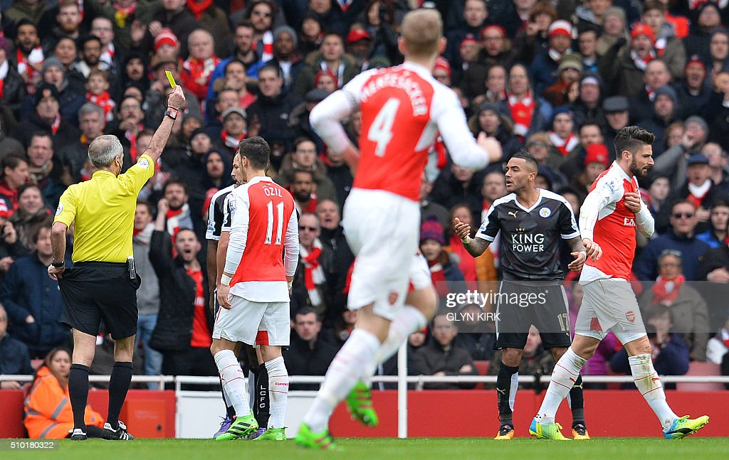 Leicester City's English defender Danny Simpson (R) reacts as referee Martin Atkinson shows him his second yellow card during the English Premier League football match between Arsenal and Leicester at the Emirates Stadium in London on February 14, 2016. / AFP / GLYN KIRK / RESTRICTED TO EDITORIAL USE. No use with unauthorized audio, video, data, fixture lists, club/league logos or 'live' services. Online in-match use limited to 75 images, no video emulation. No use in betting, games or single club/league/player publications. /
